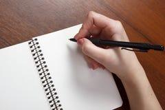 Anteckningsbok och penna i hand bakgrund isolerad white Royaltyfri Fotografi