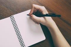 Anteckningsbok och penna i hand bakgrund isolerad white Arkivfoto