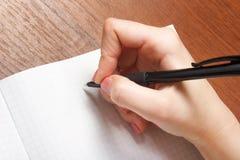 Anteckningsbok och penna i hand På vitbakgrund Royaltyfri Foto