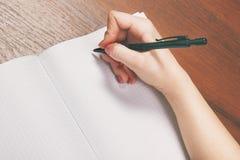 Anteckningsbok och penna i hand På vitbakgrund Royaltyfria Bilder