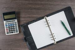 Anteckningsbok och penna med räknemaskinen på skrivbordet Arkivfoto