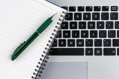 Anteckningsbok och penna på bärbar datortangentbordet, slut upp Arkivfoton