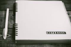 Anteckningsbok och penna på viten Arkivbild