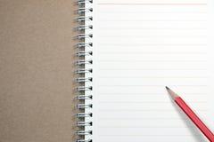Anteckningsbok och röd blyertspenna Royaltyfri Fotografi