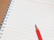 Anteckningsbok och röd blyertspenna Arkivbilder