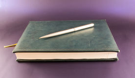 Anteckningsbok- och silverpenna Arkivbilder