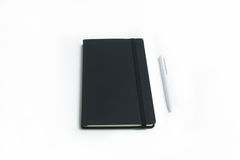 Anteckningsbok- och vitpenna royaltyfri fotografi