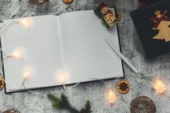 Anteckningsbok på bakgrunden av julgranleksaker girlander ovanför sikt Utrymme för text arkivbilder