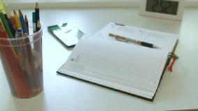 Anteckningsbok på skrivbordet arkivfilmer
