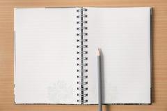Anteckningsbok på trätabellen med blyertspennan Arkivbild