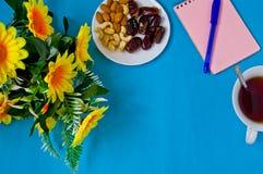 Anteckningsbok, penna, blommor och en kopp te, kvinnlig arbetsplats royaltyfria foton