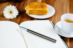 Anteckningsbok, penna, espresso och giffel royaltyfri bild