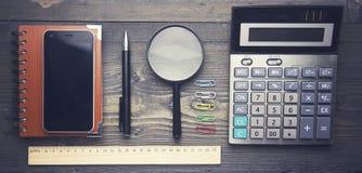 Anteckningsbok, penna, läs- exponeringsglas och räknemaskin Royaltyfri Foto
