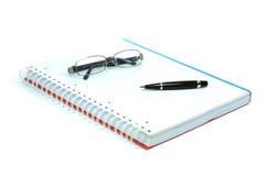 Anteckningsbok, penna och exponeringsglas Arkivfoto