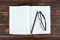 Anteckningsbok, penna och exponeringsglas på en trätabell kopiera avst?nd royaltyfria foton