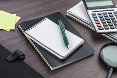 Anteckningsbok, penna och förstoringsapparat med räknemaskinen på skrivbordet Royaltyfri Bild