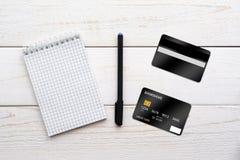 Anteckningsbok, penna och kreditkort på en vit tabell Royaltyfria Bilder