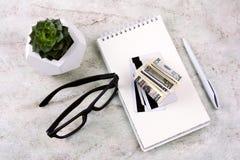 anteckningsbok, penna, pengar, kreditkortar, exponeringsglas och suckulent för lägenhet lekmanna- på en marmortabell royaltyfria foton
