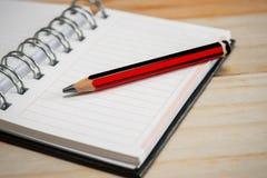 Anteckningsbok som är öppen i skrivbord Royaltyfri Fotografi