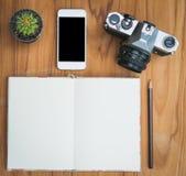 Anteckningsbokblyertspenna och kamera på wood bakgrund med kaktuns Royaltyfri Foto