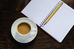 Anteckningsbokblyertspenna och kopp kaffe i den wood tabellen Royaltyfria Foton