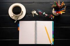 Anteckningsbokblyertspenna och kopp kaffe i den wood tabellen Royaltyfri Fotografi
