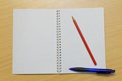 Anteckningsbokblyertspenna och penna Royaltyfri Fotografi