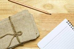 Anteckningsbokblyertspenna och säck på trätabellen Arkivbild