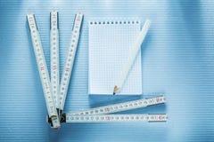 Anteckningsbokblyertspenna som mäter bandkonstruktionsbegrepp Fotografering för Bildbyråer