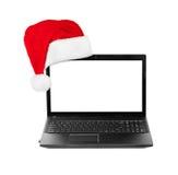 Anteckningsbokdator och Santa Claus röd julhatt Arkivfoto