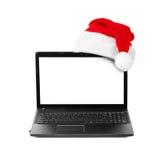 Anteckningsbokdator och Santa Claus röd julhatt Arkivbild