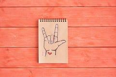 Anteckningsboken av Kraft papper med ett målat språk för amerikanskt tecken för symbolASL ILY älskar jag dig som ligger på den te royaltyfria bilder