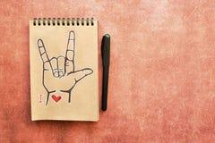 Anteckningsboken av Kraft papper, med ett målat symbol för språk för amerikanskt tecken för ASL älskar jag dig ILY Passande för l arkivfoto