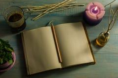 Anteckningsboken blyertspenna, vädrade stearinljus, nödvändiga oljor, trädfilialer, små träd i krukor, kaffekoppar På en trätabel Arkivfoton