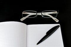 Anteckningsboken exponeringsglas och skrivar och på en svart bakgrund royaltyfri fotografi