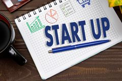 Anteckningsboken med anmärkningar STARTAR UPP på kontorstabellen med hjälpmedel arkivfoto