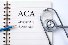 Anteckningsboken och blyertspennan med som man har råd med omsorg för ACA agerar på tabellen Arkivfoto