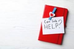 Anteckningsboken och kortet med uttryck KAN OSS HJÄLPA? på vit träbakgrund arkivfoto