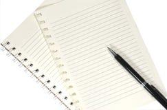 Anteckningsboken och skrivar på det trä bordlägger Arkivfoton