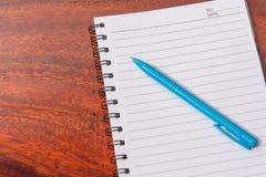 Anteckningsboken och skrivar på träskrivbordet Royaltyfria Bilder