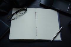 Anteckningsboken på skrivbordet, tömmer utrymme på anteckningsboken för Enter text arkivfoto