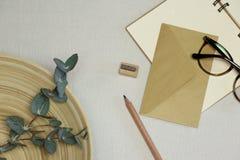 Anteckningsboken, träblyertspennan & vässaren, kuvert, anblickar, eukalyptusfilialer i korgen royaltyfri foto