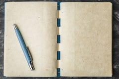 Anteckningsbokpapper med texturen och penna Arkivbilder
