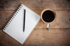 Anteckningsbokpapper och kaffe Arkivbild