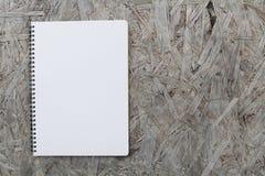 Anteckningsbokpapper på wood bakgrund Arkivbilder