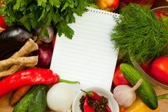Anteckningsbokpapper som skriver recept och grönsaker Royaltyfria Foton