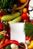 Anteckningsbokpapper som skriver recept och grönsaker Arkivfoto