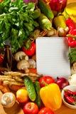Anteckningsbokpapper som skriver recept och grönsaker Arkivfoton