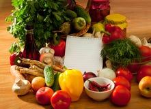 Anteckningsbokpapper som skriver recept och grönsaker Arkivbild