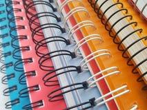 Anteckningsbokspiral Bunt av färgrika förskriftsböcker bakgrund isolerad white Anteckningsbokfärg - rosa färg, apelsin, blått royaltyfri fotografi